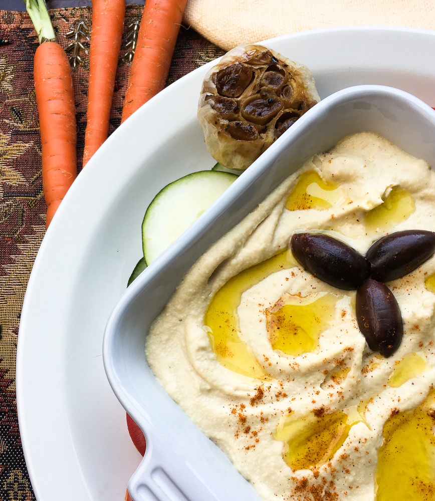 Hummus in a casserole dish with olives and vegetables