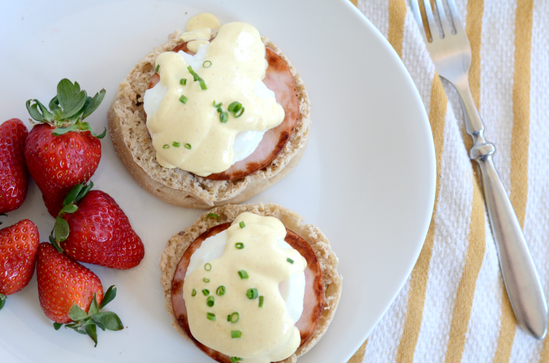 Eggs Benedict on white plate with strawberries