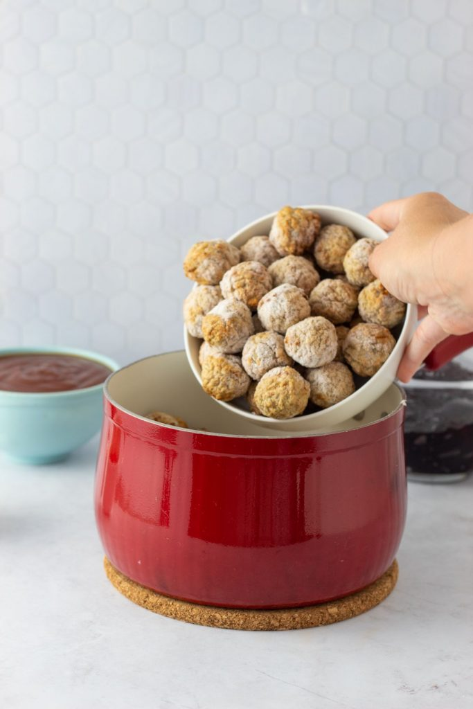 adding meatballs to a pot