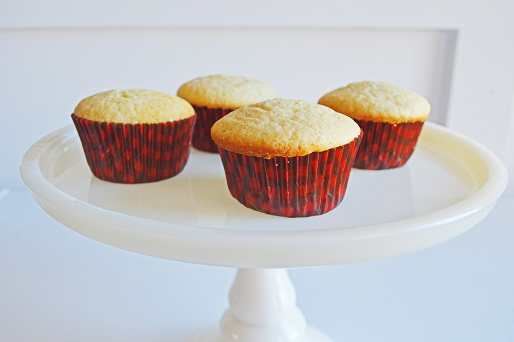 vanilla cupcakes unfrosted on a cake plate