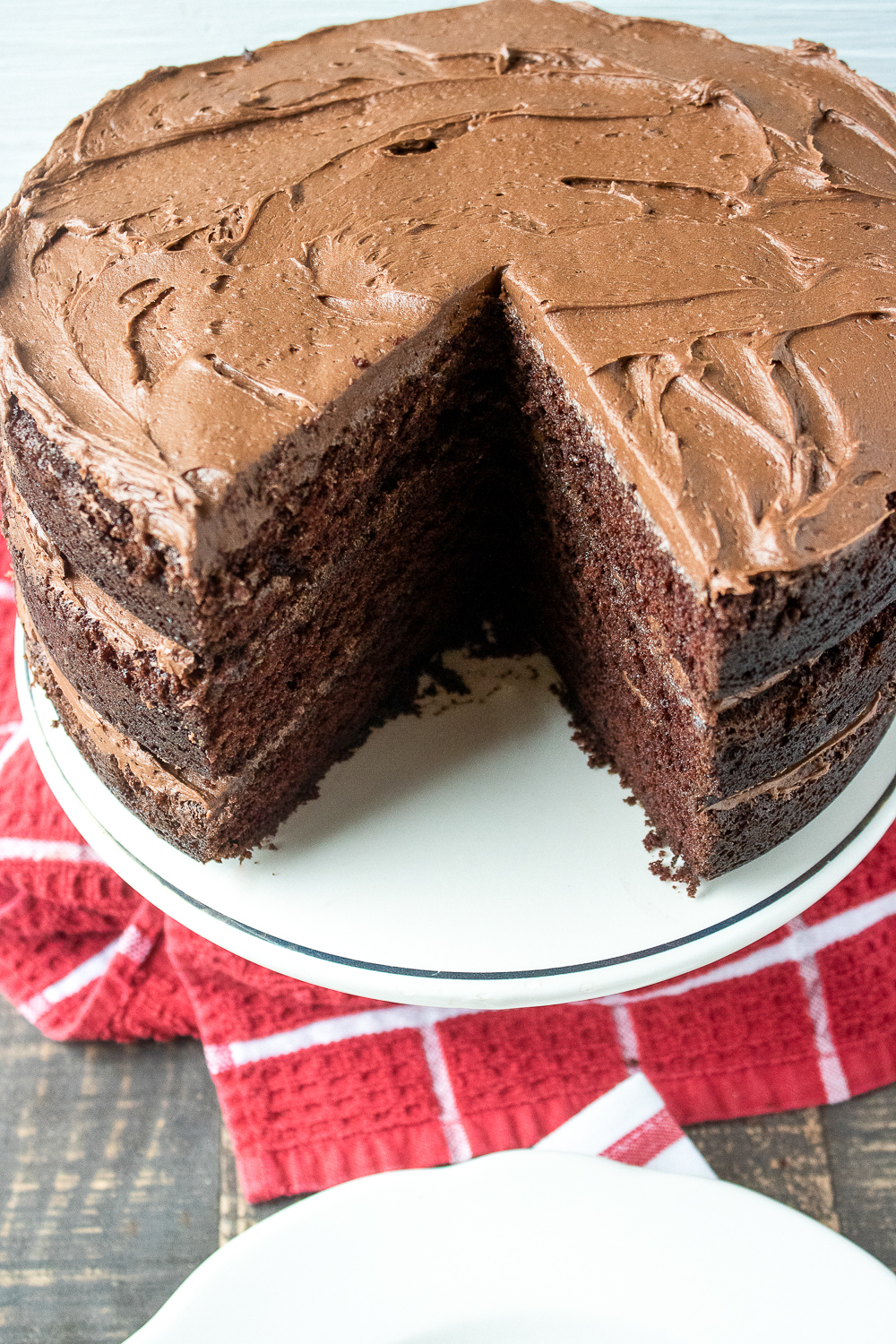 The best chocolate cake recipe with a big piece taken out on a red towel and white cake stand