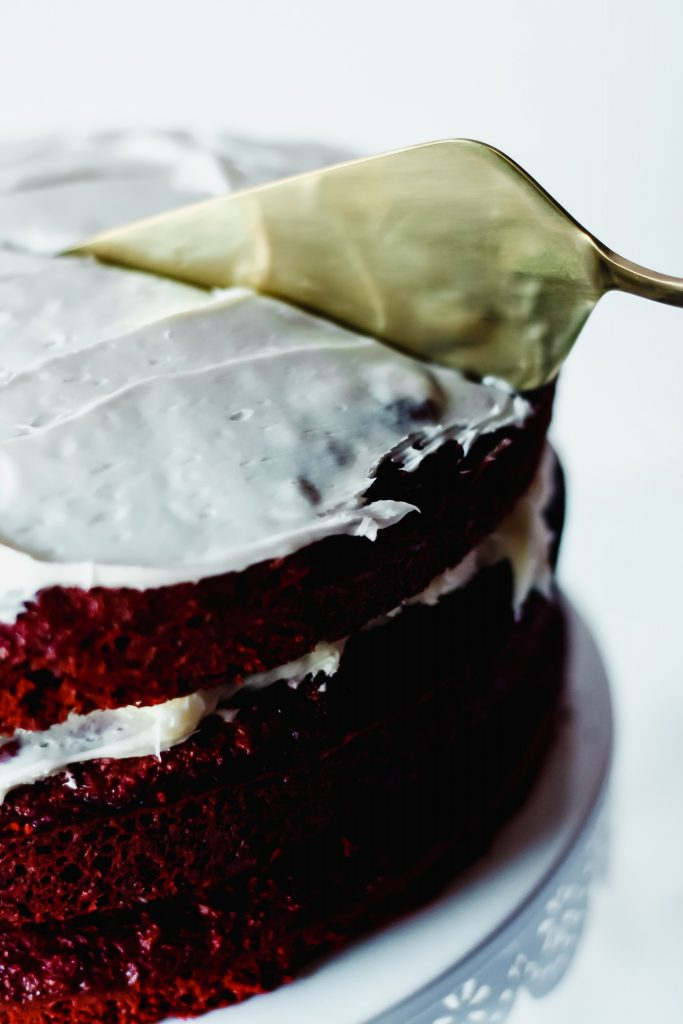 Slicing into a piece of red velvet cake
