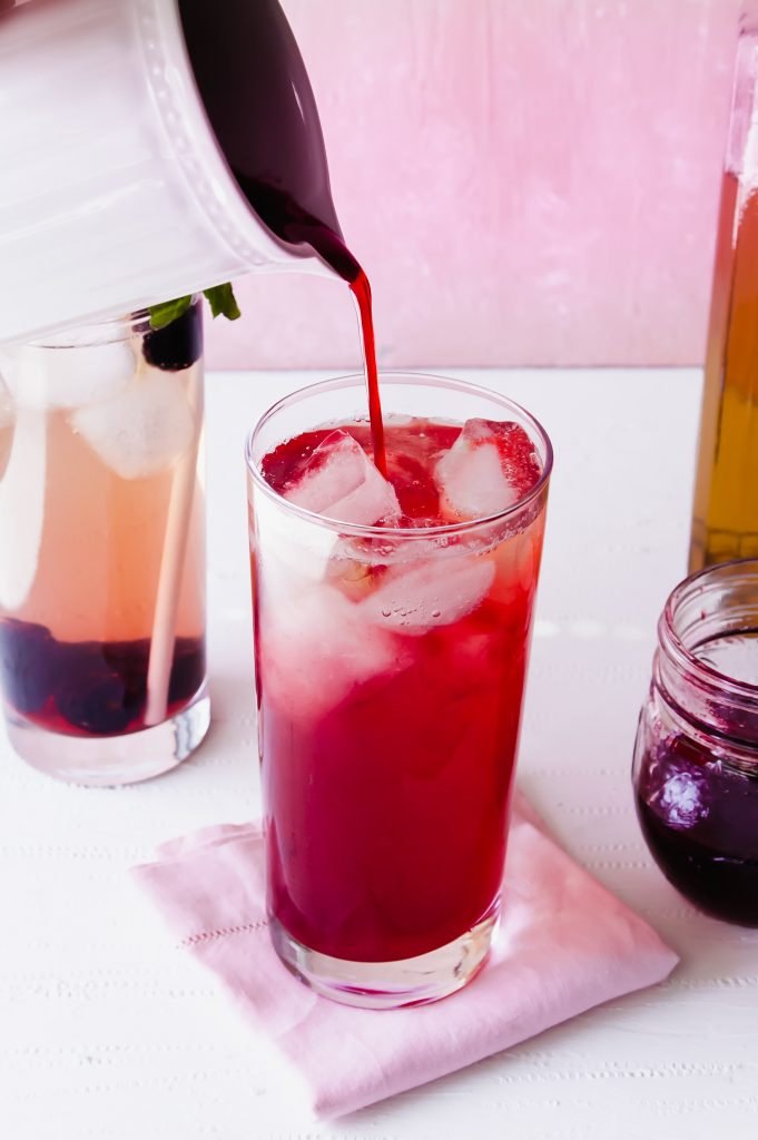 Pouring blackberry simple syrup into iced tea