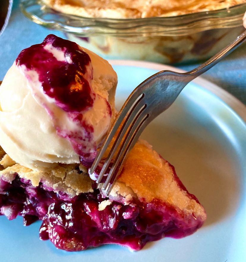 Putting a fork into a piece of blueberry pie with ice cream