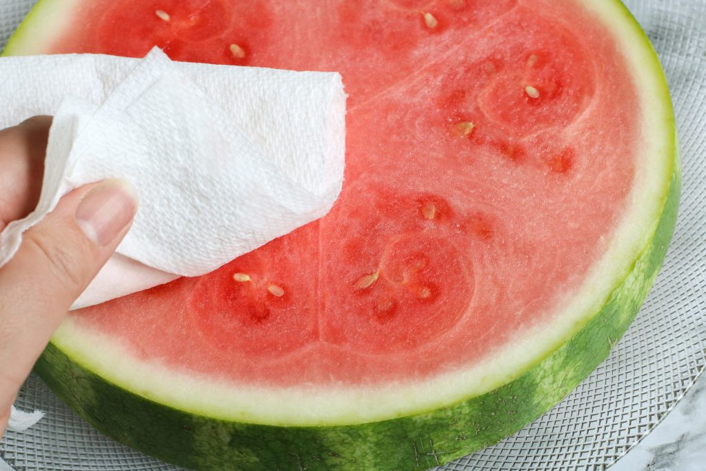 Patting watermelon slices with a paper towel