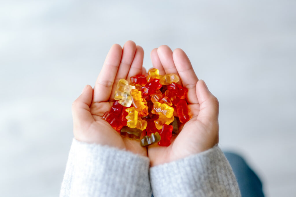 Top view image of a woman holding colorful Jelly gum in hands
