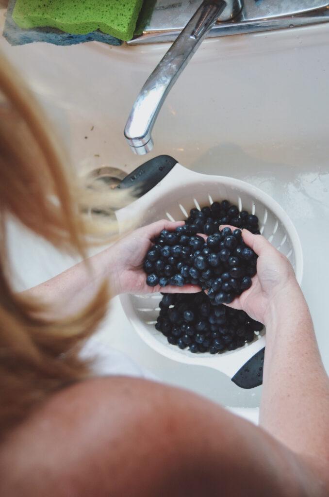 woman washing blueberries